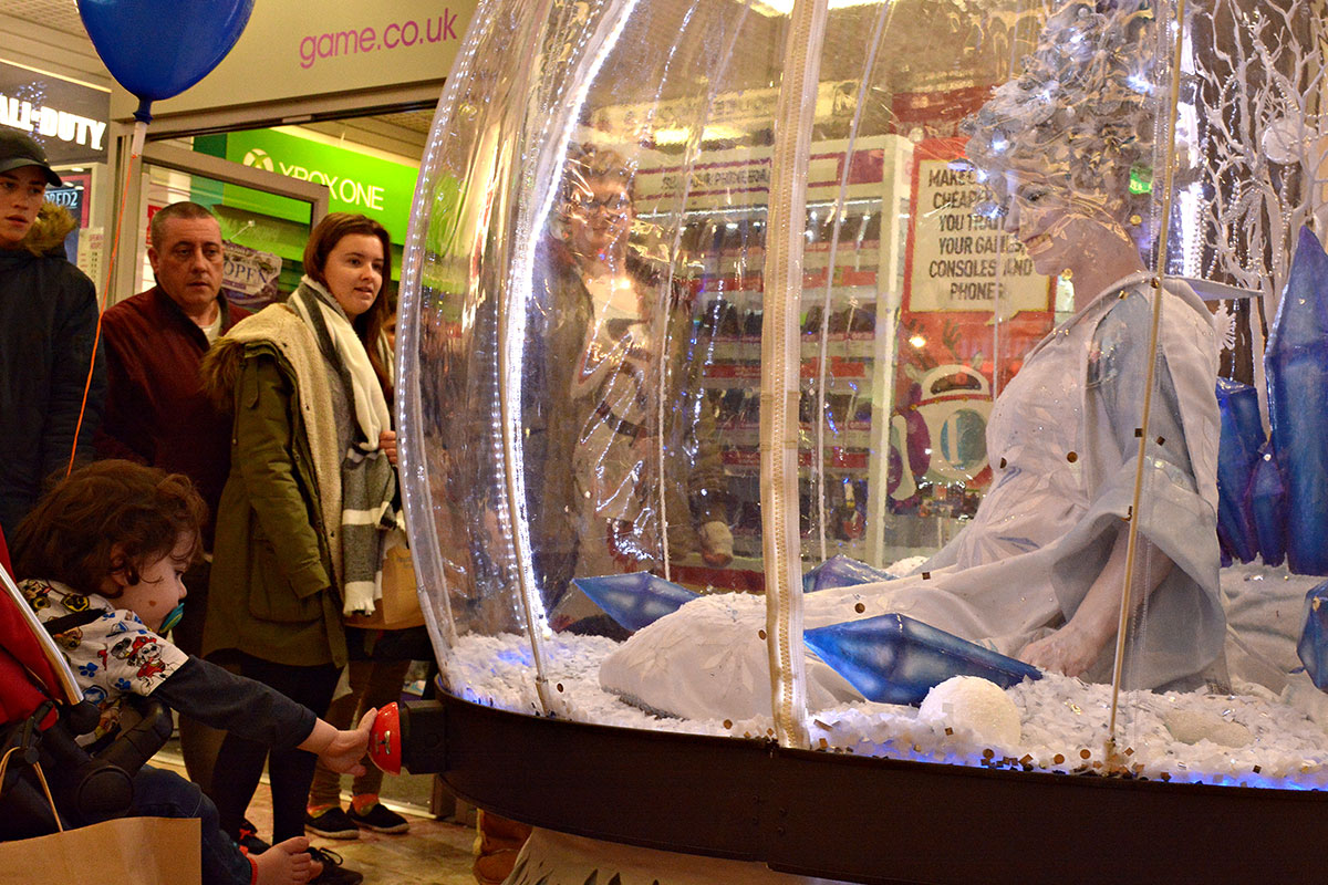 Pressing the button to trigger the snow! Christmas shopping centre act, Living Snow Globe